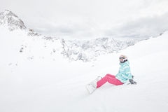 Young sitting woman with snowboard Stock Image