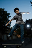 Young skate boarder. Young asian boy outside in the evening balancing on a skateboard with dark blue evening sky Stock Photo