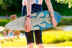 Young skateboard girl holding her longboard outdoors on sunset Royalty Free Stock Image