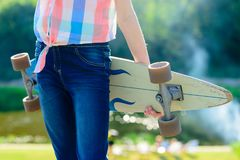 Young skateboard girl holding her longboard outdoors on sunset Royalty Free Stock Photos