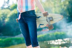 Young skateboard girl holding her longboard outdoors on sunset Royalty Free Stock Photography