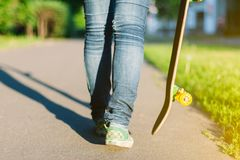 Young skateboarder girl walking with her skateboard in park, outdoors. Sport and healthy lifestyle concept. Extreme trick on skateboard. Summer, outdoors stock images