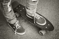 Young skateboarder in gumshoes and jeans Stock Photos