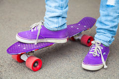Young skateboarder in gumshoes and jeans stands Royalty Free Stock Photography