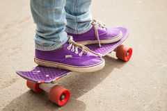 Young skateboarder in gumshoes standing on his skate Royalty Free Stock Photography