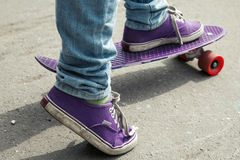 Young skateboarder in jeans riding on his skate Stock Photography