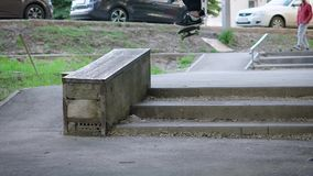 Young skateboarder jumping over the steps doing ollie trick in the street. Boy dressed in casual clothes spending stock video footage