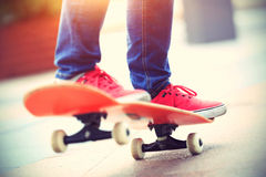 Young skateboarder legs riding on skateboard Stock Images