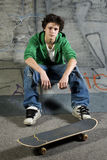 Young skateboarder looking at camera. Sitting on ramp Stock Photography