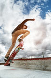 A young skateboarder makes Wallie in a skatepark, jumping on a skateboard into the air with a coup Stock Photography