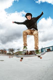 A young skateboarder makes Wallie in a skatepark, jumping on a skateboard into the air with a coup Stock Image