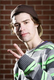 Young skateboarder making peace sign Stock Photography