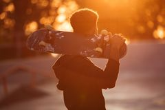 Young skateboarder man holding skateboard. On his shoulders at public park Royalty Free Stock Image