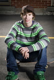 Young skateboarder sitting on his board Royalty Free Stock Images