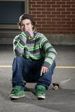 Young skateboarder sitting on his board Stock Photo