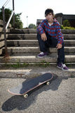Young skateboarder sitting on stairs Stock Images