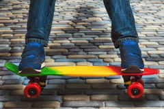 A young skateboarder in sneakers and jeans, standing on his skate. Closeup fragment of the skateboard and feet. Closeup fragment of the skateboard and feet stock photos