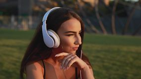 Young skateboarder woman sitting and puts on headphones stock video