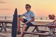 Young skater boy in sunglasses dressed in t-shirt and shorts sitting on a bench against the background of the seacoast. Young skater boy in sunglasses dressed in royalty free stock photography