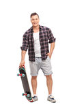 Young skater holding a skateboard. Full length portrait of a young skater holding a skateboard and looking at the camera isolated on white background Stock Images