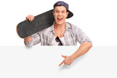 Young skater pointing on a blank signboard Royalty Free Stock Photos