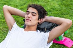 Young male skater resting on the grass with his eyes closed. stock images