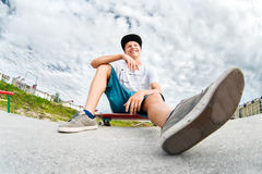 Young skater resting sitting on his skateboard in a skatepark Stock Images