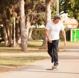 Young skater rolling down the street Stock Photo