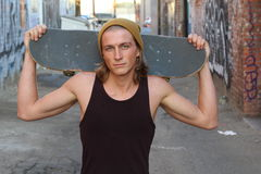 Young skater in a tank top shirt and beanie holding a skateboard over his shoulder and looking at the camera isolated on alleyway. Urban background Royalty Free Stock Photo