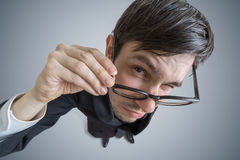 Young skeptic man with glasses is looking at you. View from above.  Stock Image