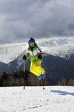 Young skier jump with ski poles in sun winter mountains and clou Stock Photo