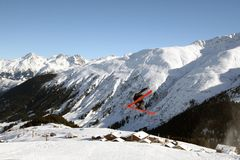 Young Skier Jumping High. Skier jumping high in the air in front of a mountain scenery Royalty Free Stock Photos