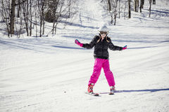 Young skier learning to ski downhill. Cute young female skier skiing down a snowy slope on a winter day at a beautiful ski resort in the rocky mountains. She is Royalty Free Stock Photos
