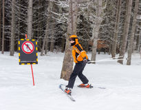 Young skier near a warning sign Royalty Free Stock Photos