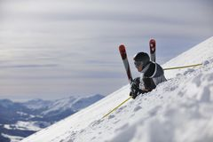 Young skier relaxing at beautiful sunny winter day. Young skier relaxing in snow and looking mountain range at beautiful sunny winter day Royalty Free Stock Photos