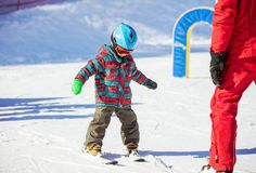 Young skier and ski instructor on slope in beginners` area Stock Images