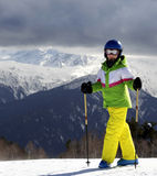 Young skier with ski poles at sun mountains and cloudy gray sky Stock Images