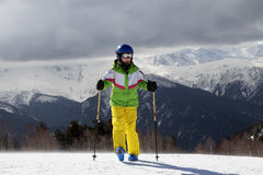Young skier with ski poles in sun mountains and gray sky before Royalty Free Stock Image