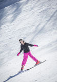 Young skier skiing downhill. Cute young female skier skiing down a snowy slope on a winter day at a beautiful ski resort in the rocky mountains. She is happy and Royalty Free Stock Photo