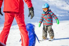 Young skier sliding down towards towards toy penguin and ski ins Royalty Free Stock Photo