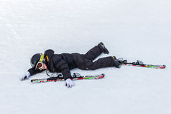 Young skier tiered on the slope. Young skier lying on the ski slope Stock Photography
