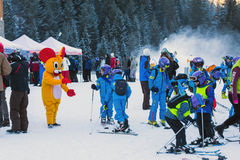 Young skiers preparing to ski and Mouse in Costume Stock Image