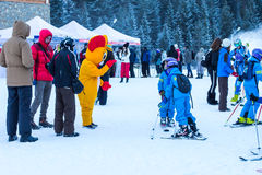 Young skiers preparing to ski and Mouse in Costume Royalty Free Stock Image