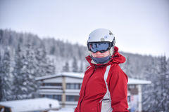 Young skiing woman with black goggles, white helmet and red jacket, winter resort in background Stock Photo