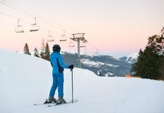 Skiing woman standing in snow mountain against ski-lift Stock Photos