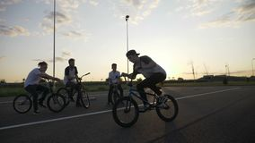 Young skilled biker practicing acrobatic technique of 360 rotation with his friends outside in slow motion -. Young skilled biker practicing acrobatic technique stock video footage
