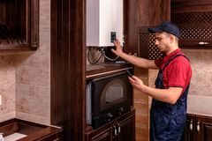 A young skilled worker regulates the gas boiler before use royalty free stock photography