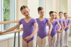 Young skillful ballerinas performing ballet exercise. Female ballet dancers having practice. Rehearsal of dance element at ballet barre in studio Stock Photos