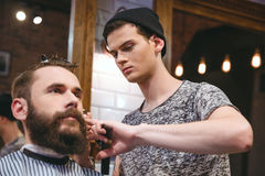 Young skillful barber making haircut to handsome bearded man. Young skillful barber making haircut to handsome bearded men in barbershop Royalty Free Stock Photos
