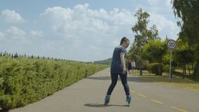 Active female roller riding backwards in park. Young skillful woman rollerblading backwards along path of well-kept public park. Female skater showing skill of stock video